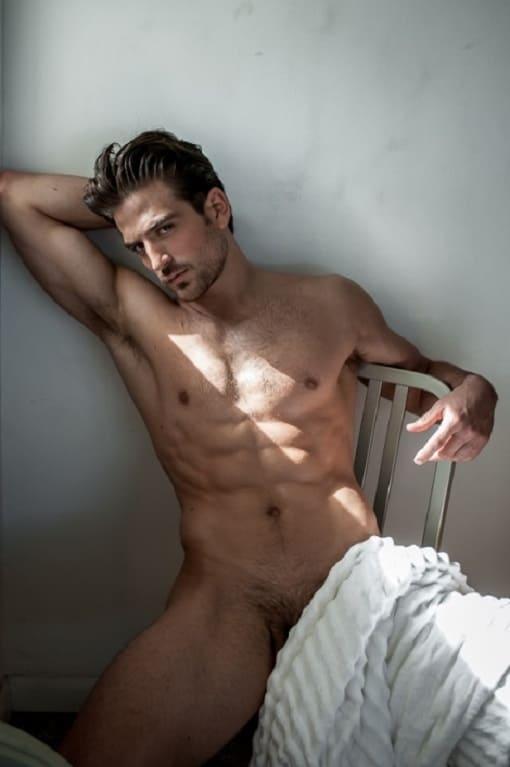 Foto do modelo Jacob Burton sentado sem roupa nenhuma.