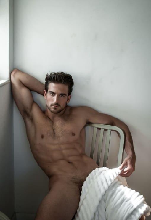 Foto de Jacob Burton sentado sem camisa tampando a pica.